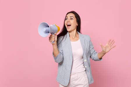 Portrait of cheerful young woman in striped jacket looking aside, scream in megaphone isolated on pink pastel wall background in studio. People sincere emotions, lifestyle concept. Mock up copy space