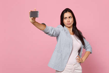 Beautiful young woman in striped jacket making duck face, doing selfie shot on mobile phone isolated on pink pastel background in studio. People sincere emotions lifestyle concept. Mock up copy space