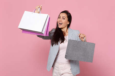 Portrait of laughing young woman in striped jacket holding package bag with purchases after shopping isolated on pink pastel background. People sincere emotions, lifestyle concept. Mock up copy space