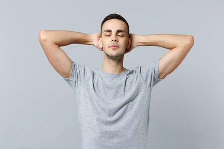 Relaxed young man in casual clothes keeping eyes closed, sleeping with hands behind head isolated on grey wall background in studio. People sincere emotions, lifestyle concept. Mock up copy space