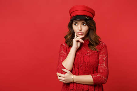 Portrait of thinkful young woman in lace dress, cap looking aside, put hand prop up on chin isolated on bright red background in studio. People sincere emotions, lifestyle concept. Mock up copy space