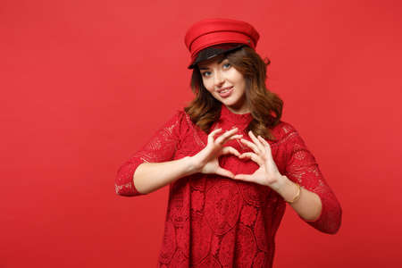 Portrait of attractive young woman in lace dress, cap showing shape heart with hands isolated on bright red wall background in studio. People sincere emotions, lifestyle concept. Mock up copy space