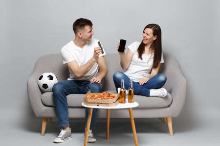 Laughing couple woman man football fans cheer up support favorite team holding mobile phone with blank empty screen isolated on grey background. People emotions sport family leisure lifestyle concept