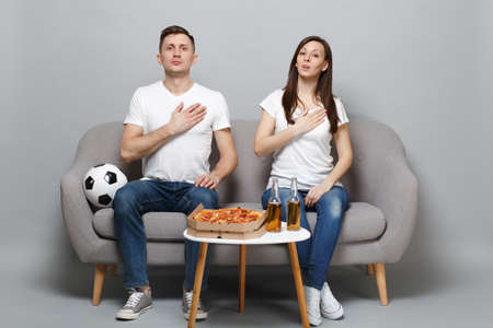 Couple woman man football fans in white t-shirt cheer up support favorite team singing hymn with hand on chest isolated on grey wall background. People emotions sport family leisure lifestyle concept Stock Photo