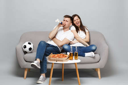 Crazy couple woman man football fans in white t-shirt cheer up support favorite team blowing in pipe, sitting isolated on grey wall background. People emotions, sport family leisure lifestyle concept Standard-Bild