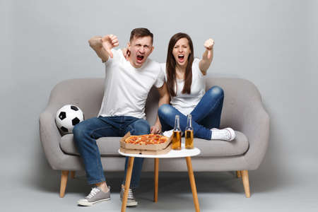 Angry couple woman man football fans cheer up support favorite team expressive gesticulating hands, showing thumb down isolated on grey wall background. People emotions sport family lifestyle concept