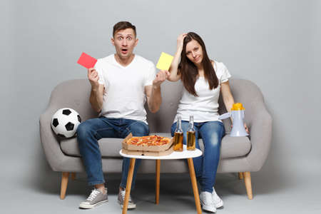 Couple woman man football fans cheer up support favorite team holding megaphone yellow and red card isolated on grey wall background in studio. People emotions, sport family leisure lifestyle concept