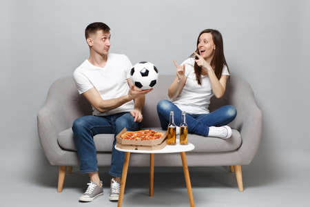 Fun couple woman man football fans cheer up support favorite team with soccer ball, pointing index fingers isolated on grey wall background. People emotions, sport family leisure lifestyle concept