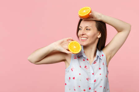 Smiling young woman in summer clothes looking aside holding two halfs of fresh ripe orange fruit isolated on pink pastel background. People vivid lifestyle relax vacation concept. Mock up copy space Stockfoto