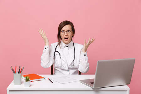 Tired sad female doctor sits at desk work on computer with medical document in hospital isolated on pastel pink wall background. Woman in medical gown glasses stethoscope. Healthcare medicine concept