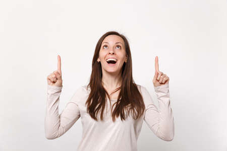 Portrait of cheerful excited young woman in light clothes looking pointing index fingers up isolated on white wall background in studio. People sincere emotions, lifestyle concept. Mock up copy space