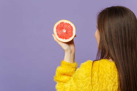 Back rear view of young woman in fur sweater holding in hand half of fresh ripe grapefruit isolated on violet pastel wall background. People vivid lifestyle relax vacation concept. Mock up copy space Stockfoto