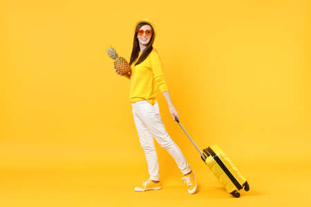 Smiling traveler tourist woman in summer clothes, hat hold fresh ripe pineapple fruit isolated on yellow orange background. Passenger traveling abroad on weekends getaway. Air flight journey concept