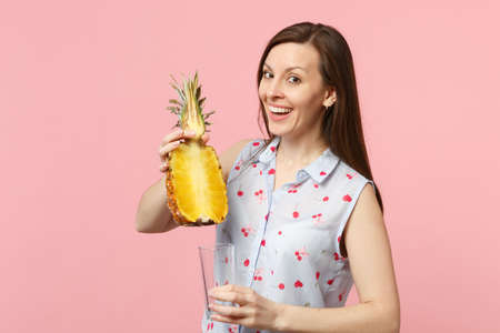 Joyful young woman in summer clothes holding half of fresh ripe pineapple fruit, glass cup isolated on pink pastel wall background. People vivid lifestyle, relax vacation concept. Mock up copy space
