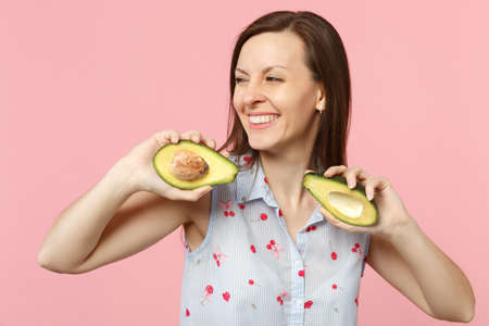 Smiling young woman in summer clothes looking aside, hold halfs of fresh ripe avocado fruit isolated on pink pastel wall background. People vivid lifestyle relax vacation concept. Mock up copy space