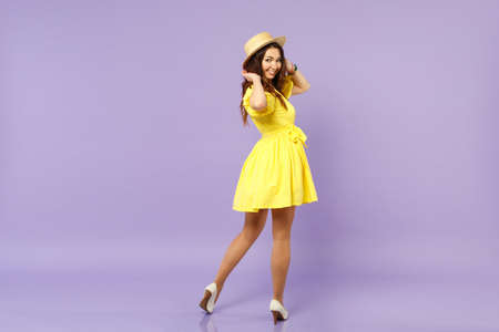 Back rear view of smiling young woman in yellow dress, summer hat looking back, rising hands isolated on pastel violet wall background. People sincere emotions, lifestyle concept. Mock up copy space Banque d'images