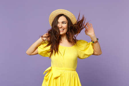Pretty young woman in yellow dress, summer hat spreading hands with fluttering hair, looking aside isolated on pastel violet background. People sincere emotions lifestyle concept. Mock up copy space