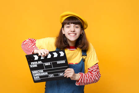 Cheerful girl teenager in french beret, denim sundress holding classic black film making clapperboard isolated on yellow wall background. People sincere emotions lifestyle concept. Mock up copy space