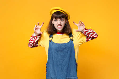 Crazy girl teenager in french beret, denim sundress growling like animal, making cat claws gesture isolated on yellow wall background in studio. People emotions, lifestyle concept. Mock up copy space Stock Photo