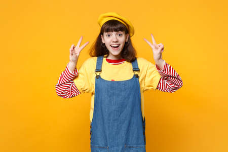 Portrait of cheerful excited girl teenager in french beret, denim sundress showing victory sign isolated on yellow background in studio. People sincere emotions, lifestyle concept. Mock up copy space