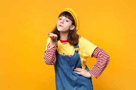 Portrait of cute girl teenager in french beret, denim sundress blowing sending air kiss isolated on yellow wall background in studio. People sincere emotions, lifestyle concept. Mock up copy space