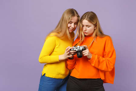Two pretty young blonde twins sisters girls in vivid colorful clothes holding retro vintage photo camera isolated on violet blue wall background. People family lifestyle concept. Mock up copy space Фото со стока