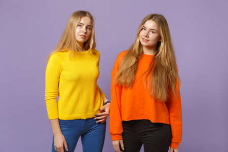 Two young blonde twins sisters girls in vivid colorful clothes standing, looking camera isolated on pastel violet blue wall background in studio. People family lifestyle concept. Mock up copy space