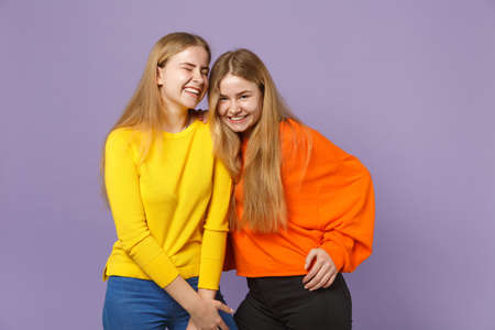 Two pretty happy young blonde twins sisters girls in vivid colorful clothes standing looking camera isolated on pastel violet blue wall background. People family lifestyle concept. Mock up copy space