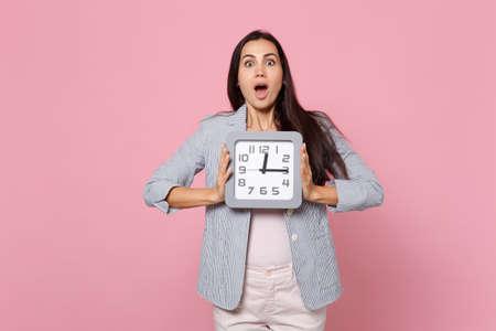 Schockierte junge Frau in gestreifter Jacke, die den Mund weit offen hält und die quadratische Uhr einzeln auf rosafarbenem Pastellwandhintergrund im Studio hält. Menschen aufrichtige Emotionen, Lifestyle-Konzept. Mock-up-Kopierraum Standard-Bild