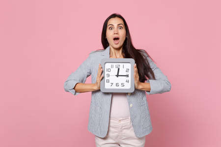 Shocked young woman in striped jacket keeping mouth wide open, holding square clock isolated on pink pastel wall background in studio. People sincere emotions, lifestyle concept. Mock up copy space