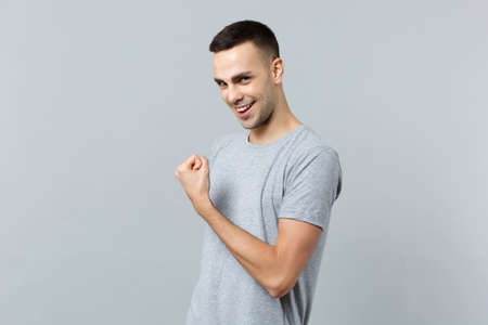 Portrait of smiling attractive young man in casual clothes looking camera, doing winner gesture isolated on grey background in studio. People sincere emotions, lifestyle concept. Mock up copy space Archivio Fotografico