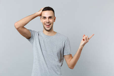 Portrait of excited young man in casual clothes putting hand on head, pointing index finger aside isolated on grey background in studio. People sincere emotions, lifestyle concept. Mock up copy space