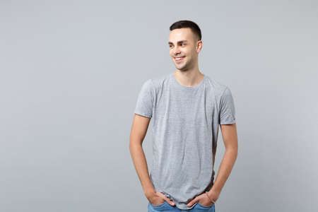 Portrait of smiling handsome young man in casual clothes looking aside, holding pockets in pockets isolated on grey wall background in studio. People sincere emotions, lifestyle concept. Mock up copy space Фото со стока
