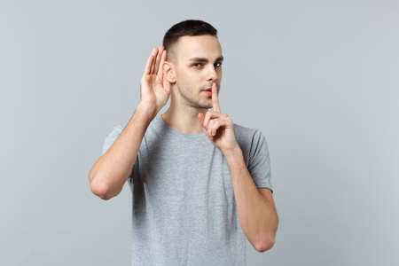 Portrait of young man eavesdrop with hearing gesture, saying hush be quiet with finger on lips shhh gesture isolated on grey background. People sincere emotions, lifestyle concept. Mock up copy space 免版税图像