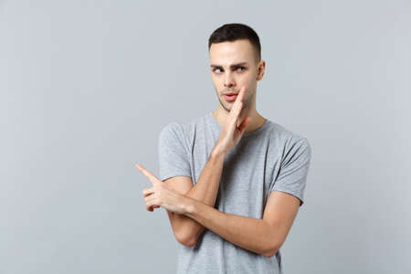 Portrait of young man in casual clothes whispering secret behind his hand, pointing index finger aside isolated on grey wall background. People sincere emotions, lifestyle concept. Mock up copy space Archivio Fotografico