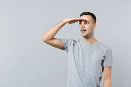 Attractive young man in casual clothes holding hand at forehead looking far away�distance isolated on grey background. People sincere emotions, lifestyle concept. Mock up copy space. Advertising area