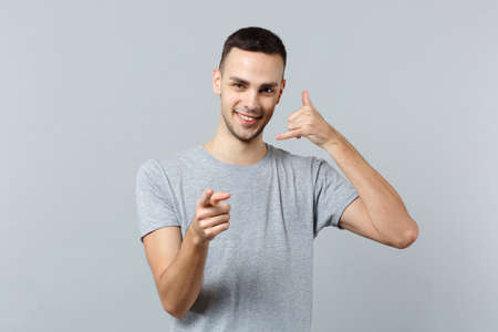 Young man in casual clothes doing phone gesture like says call me back, pointing index finger on camera isolated on grey wall background. People sincere emotions lifestyle concept. Mock up copy space