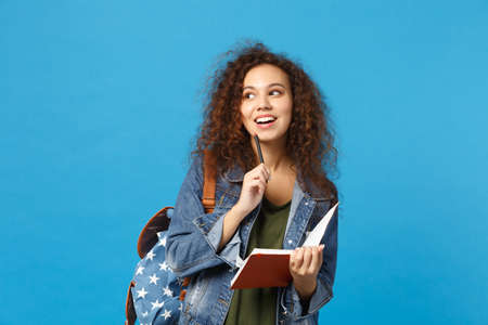 Young african american girl teen student in denim clothes, backpack hold books isolated on blue background studio portrait. Education in high school university college concept. Mock up copy space 版權商用圖片
