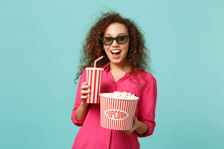 Excited african girl in 3d imax glasses watching movie film hold popcorn cup of soda isolated on blue turquoise background in studio. People emotions in cinema, lifestyle concept. Mock up copy space Archivio Fotografico