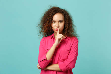 Attractive african girl in casual clothes saying hush be quiet with finger on lips shhh gesture isolated on blue turquoise background. People sincere emotions lifestyle concept. Mock up copy space