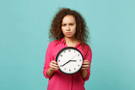 Portrait of concerned african girl in pink casual clothes holding round clock isolated on blue turquoise wall background in studio. People sincere emotions, lifestyle concept. Mock up copy space Banque d'images - 120966507