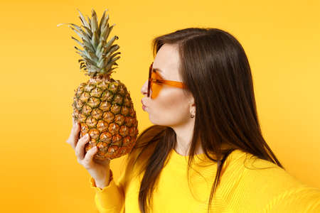 Close up selfie shot of crazy young woman in heart glasses hold, kissing fresh pineapple fruit isolated on yellow orange background. People vivid lifestyle, relax vacation concept. Mock up copy space