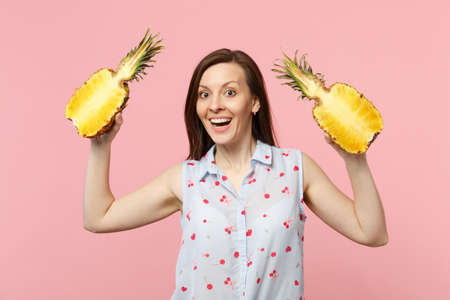 Excited young woman in summer clothes holding halfs of fresh ripe pineapple fruit isolated on pink pastel wall background in studio. People vivid lifestyle, relax vacation concept. Mock up copy space Imagens