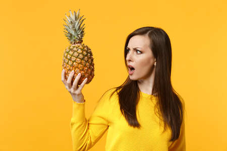 Shocked perplexed young woman in casual clothes holding, looking on fresh ripe pineapple fruit isolated on yellow orange background. People vivid lifestyle, relax vacation concept. Mock up copy space