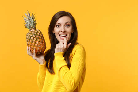 Cheerful young woman in casual clothes gnawing nails, hold in hands fresh ripe pineapple fruit isolated on yellow orange background. People vivid lifestyle, relax vacation concept. Mock up copy space