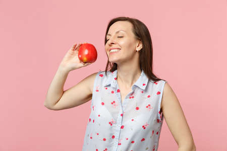 Pretty young woman in summer clothes keeeping eyes closed holding fresh ripe red apple fruit isolated on pink pastel wall background. People vivid lifestyle relax vacation concept. Mock up copy space