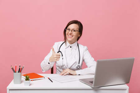 Beautiful female doctor sits at desk works on computer with medical document in hospital isolated on pastel pink background. Woman in medical gown glasses stethoscope. Healthcare medicine concept 版權商用圖片