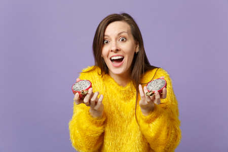 Surprised young woman in fur sweater keeping mouth open holding halfs of pitahaya, dragon fruit isolated on violet pastel background. People vivid lifestyle relax vacation concept. Mock up copy space Imagens