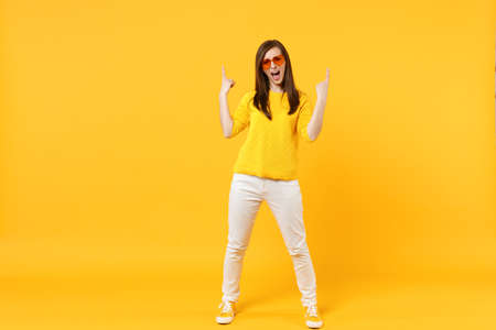 Screaming young woman in casual clothes, heart glasses pointing index fingers up isolated on yellow orange wall background in studio. People sincere emotions, lifestyle concept. Mock up copy space