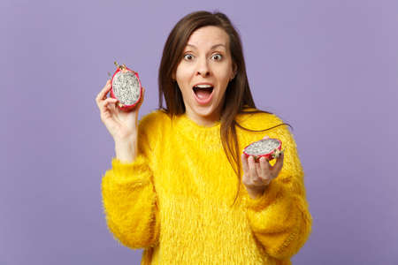 Amazed young woman in fur sweater keeping mouth open holding halfs of pitahaya, dragon fruit isolated on violet pastel background. People vivid lifestyle relax vacation concept. Mock up copy space